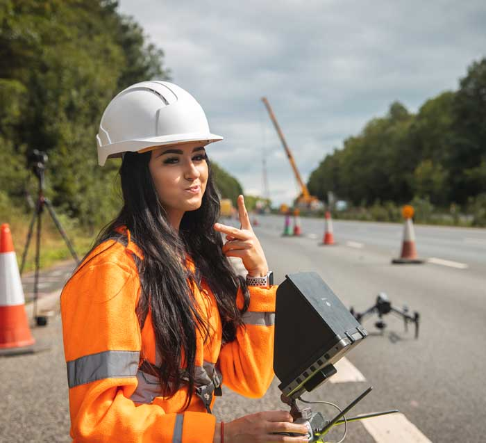 a female drone camera filming on a highway wearing PPE