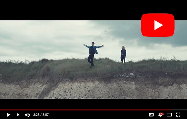 singer stood on cliff in music video filmed by drone