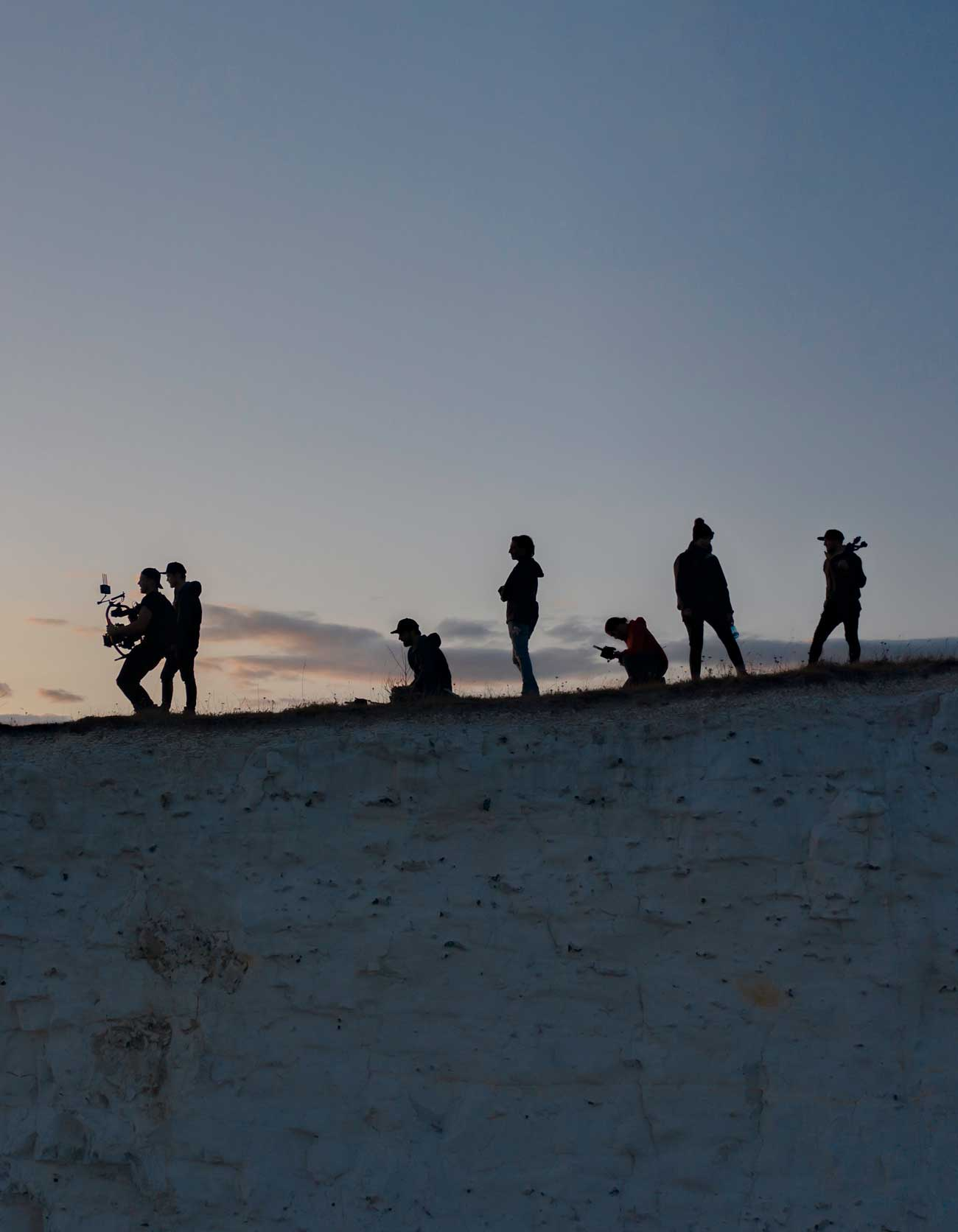 filmcrew silhouettes on a cliff edge drone photo