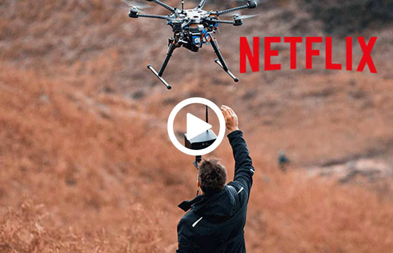 drone pilot stood under flying drone on film set