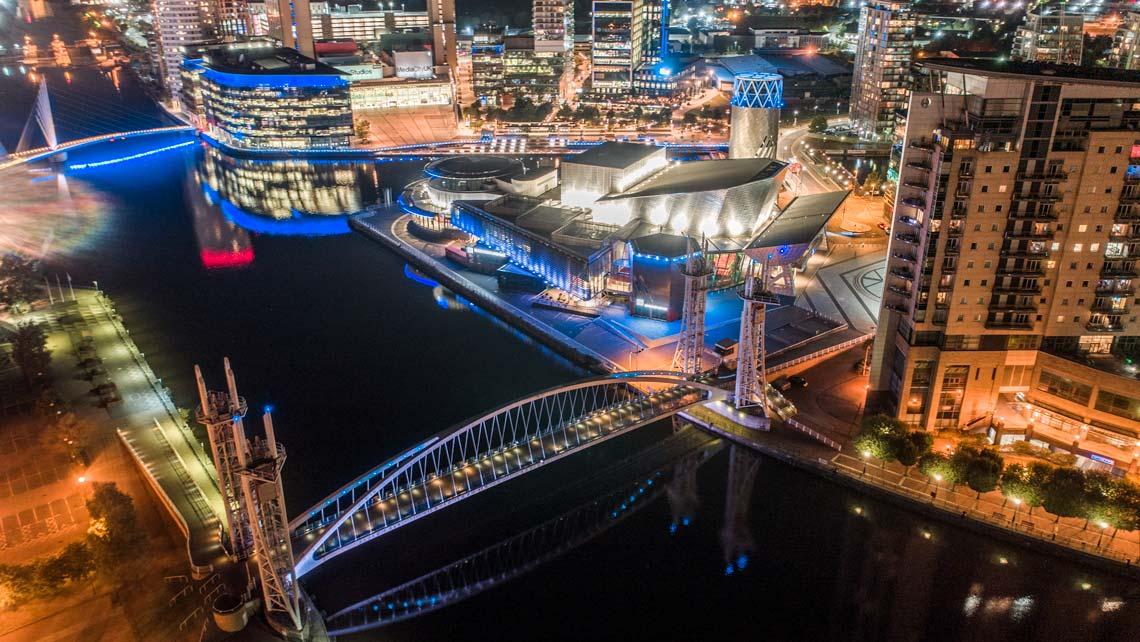 Media City in Manchester cityscape view at night taken by drone
