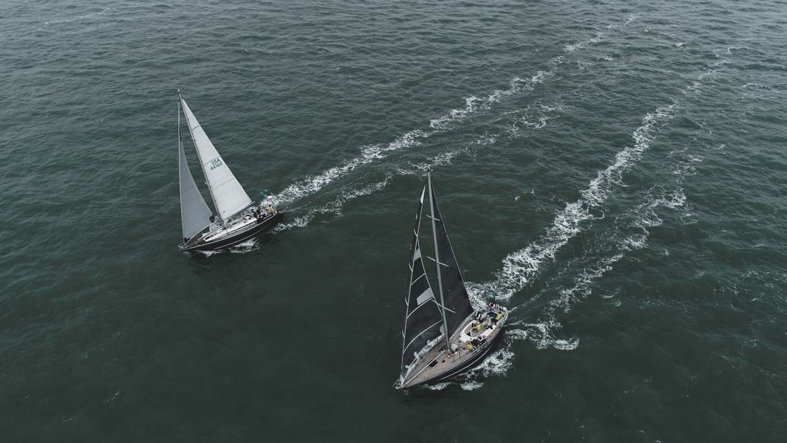 a yacht competing in a race chased by a drone