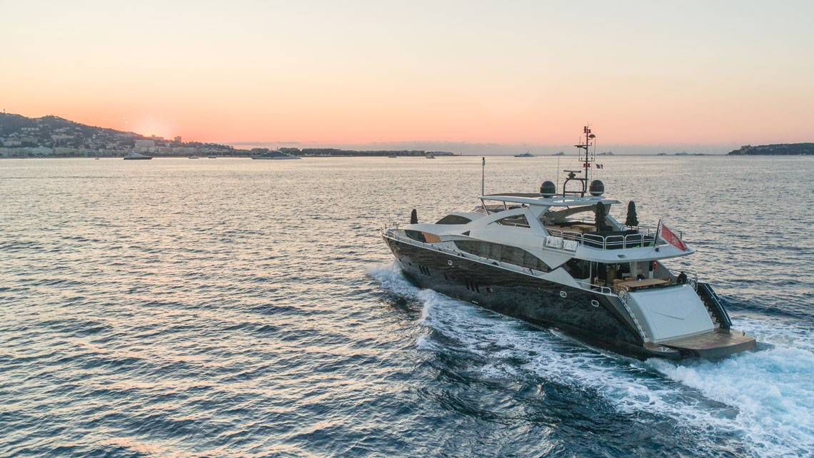 super yacht motoring at sunrise seen from the air by a drone